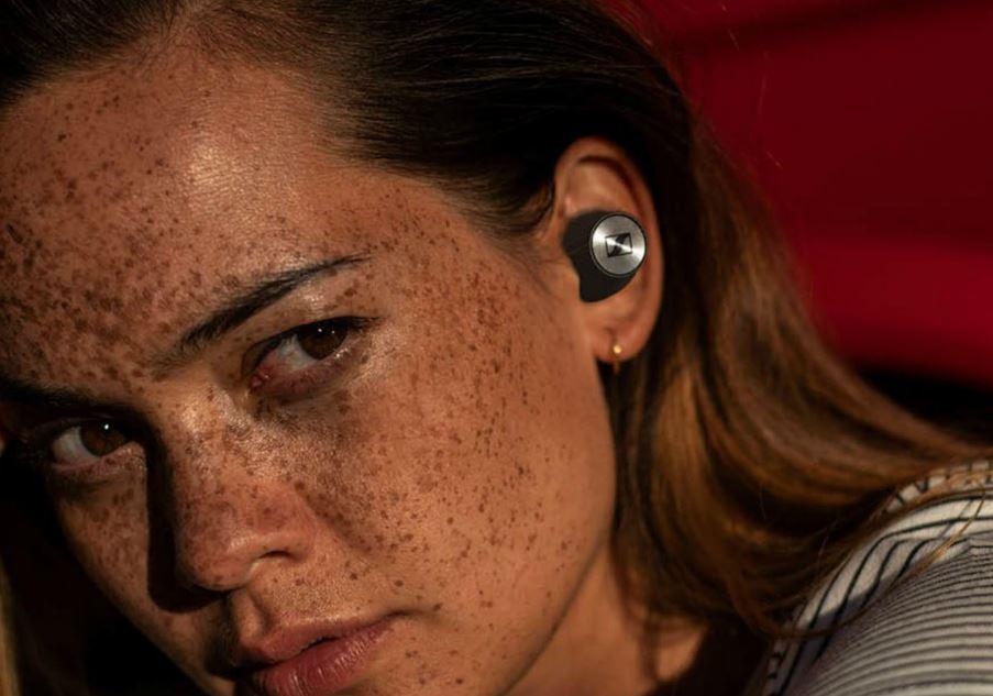 Kobieta z piegami ze słuchawką Sennheiser True Wireless